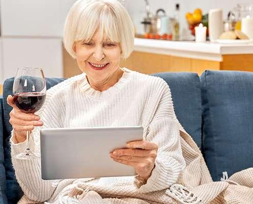 Eine ältere Dame sitzt auf der Couch und schaut auf Ihren Laptop