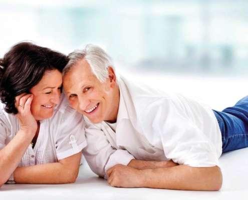 Ein älteres Paar liegt zusammen auf den Boden