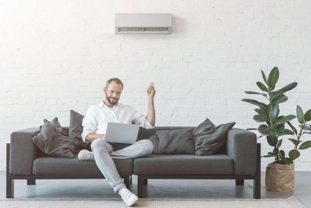 Ein Mann schaut auf seinen Laptop und bedient seine Klimaanlage mit einer Fernbedienung